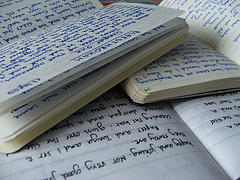 Image of several open paper notebooks open on top of one another